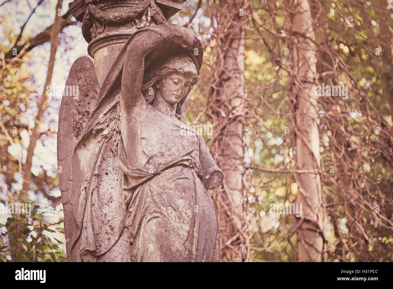 Old damaged decaying ruin angel statue on grave tomb at