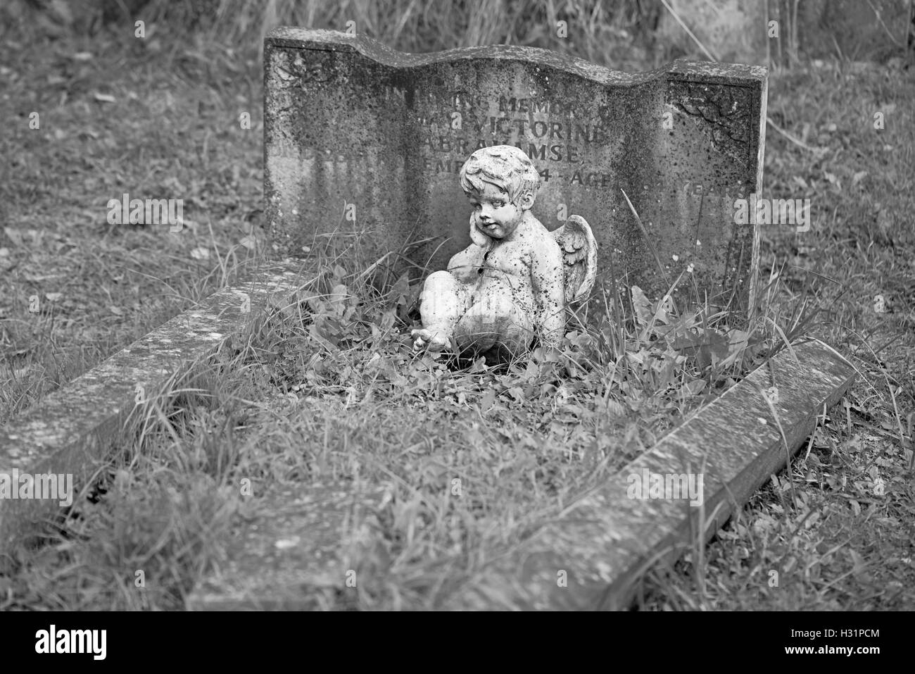 Baby little angel statue ad child's grave at Highgate Cemetery East in London, England. - Stock Image
