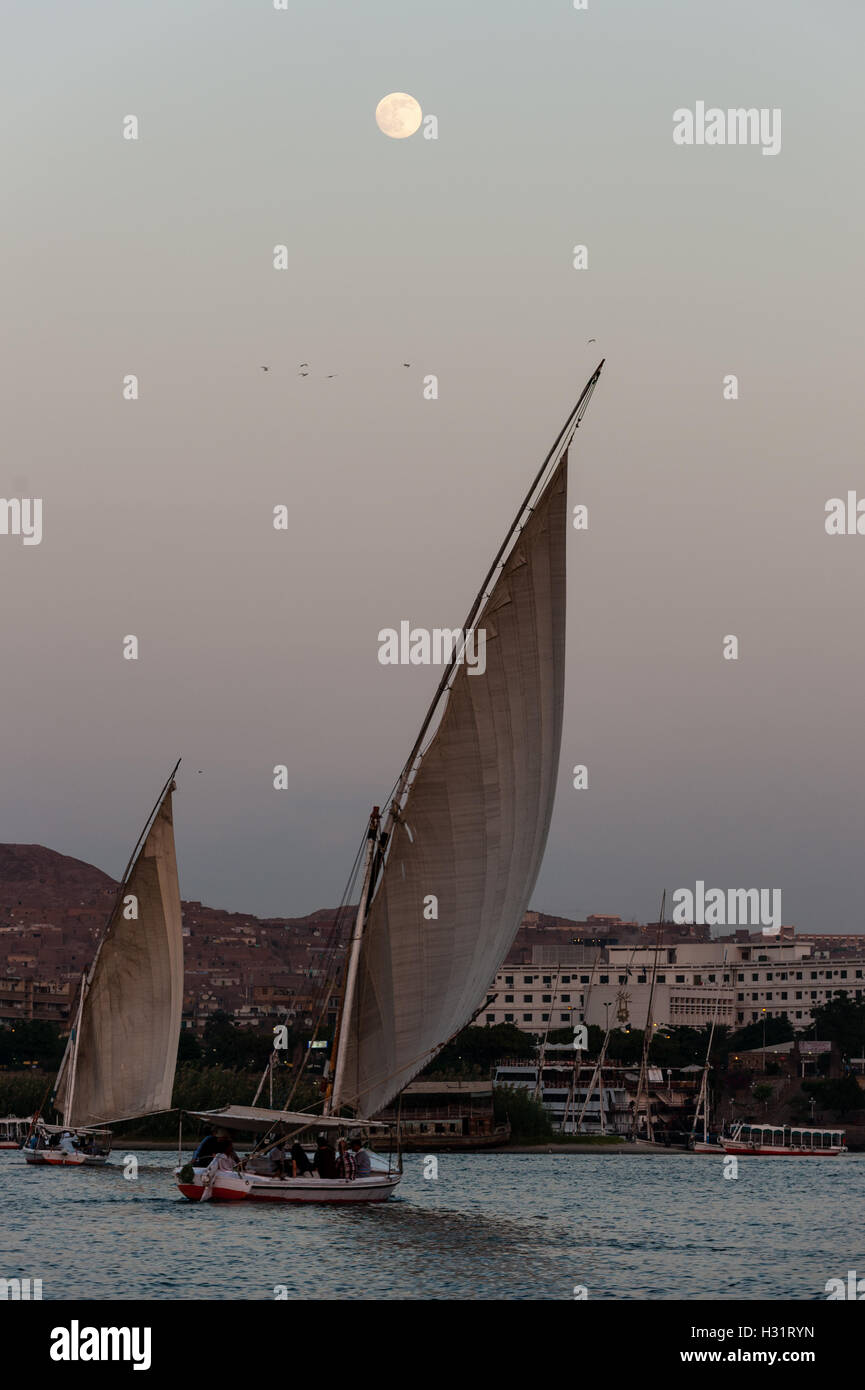 Egypt. Aswan stands on the east bank of the Nile. A felucca is a traditional wooden sailing boat, with the moon - Stock Image