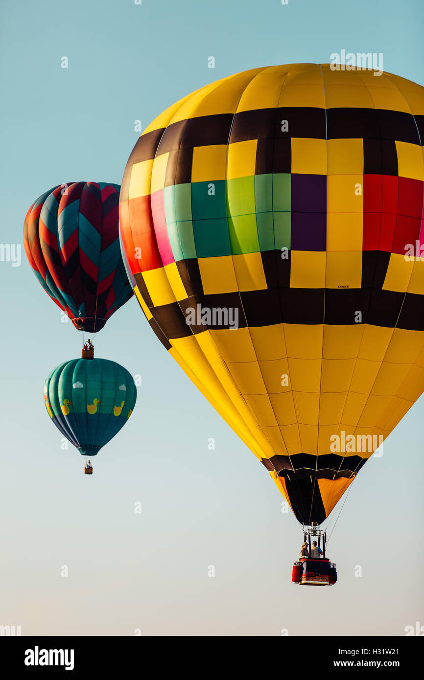 Three colorful hot air balloons isolated against a clear sky Stock Photo