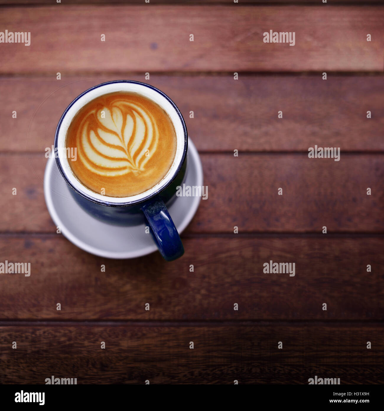 Cup of Coffee Latte on Wooden table with Natural light, selective focus on a cup Stock Photo