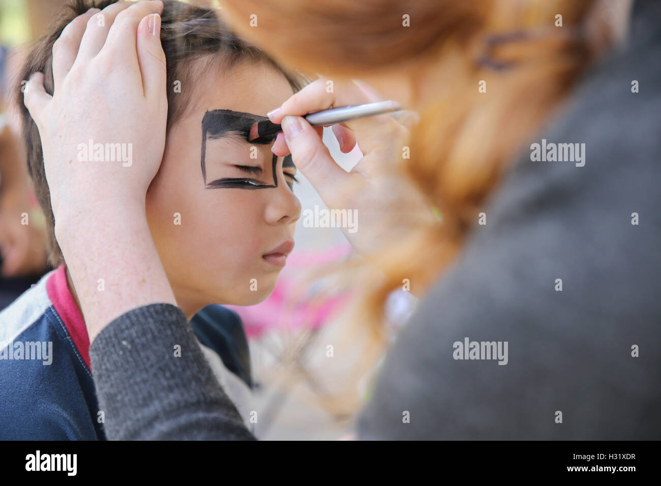 Young boy getting face painted - Stock Image