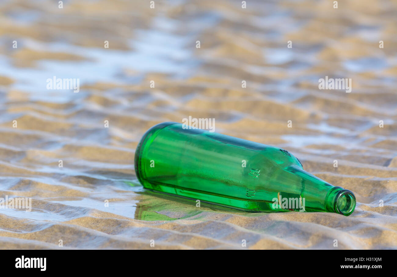 Discarded empty green bottle left on a sandy beach. - Stock Image