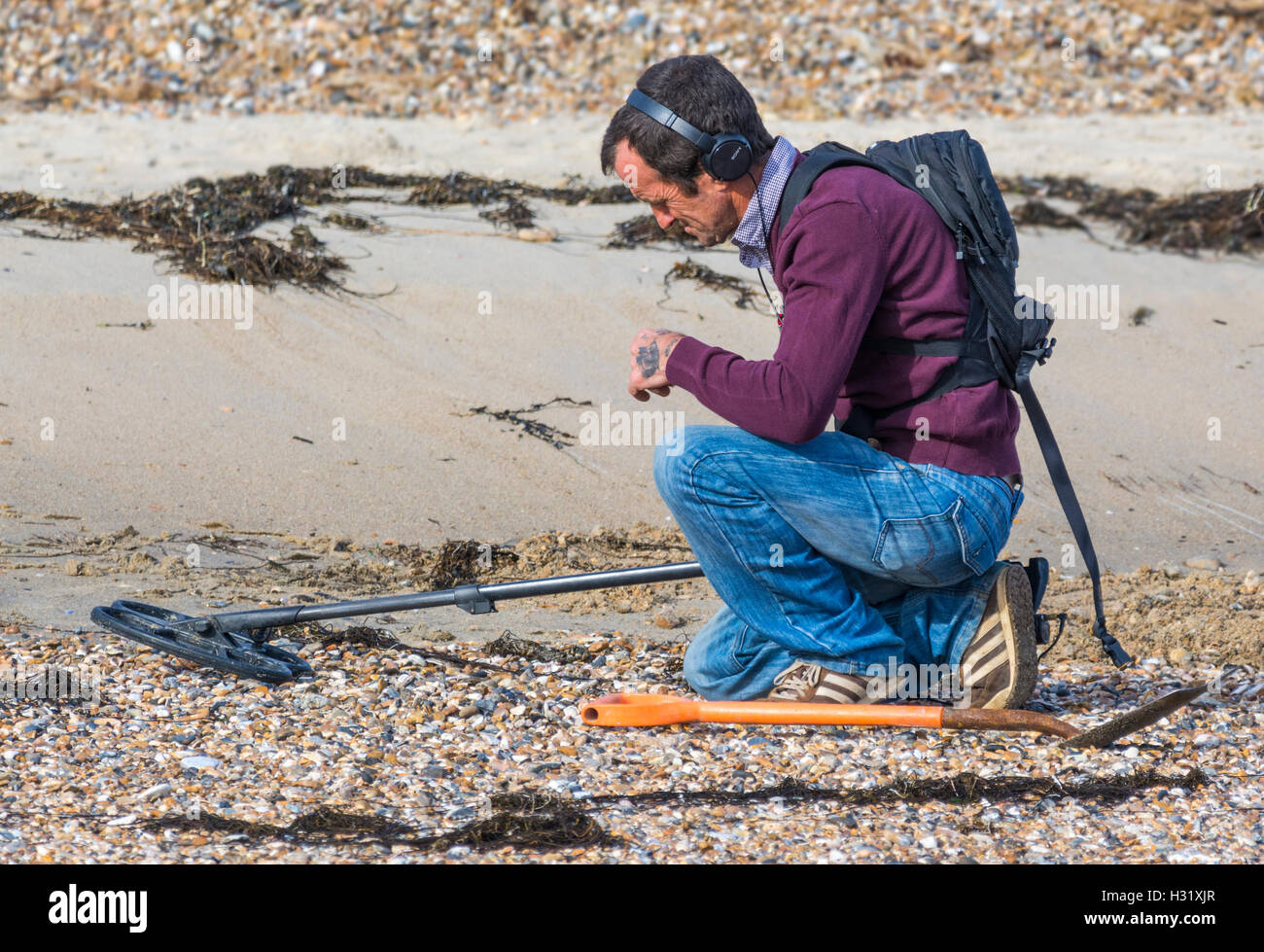 Man looking for treasure with a metal detector on a beach. - Stock Image