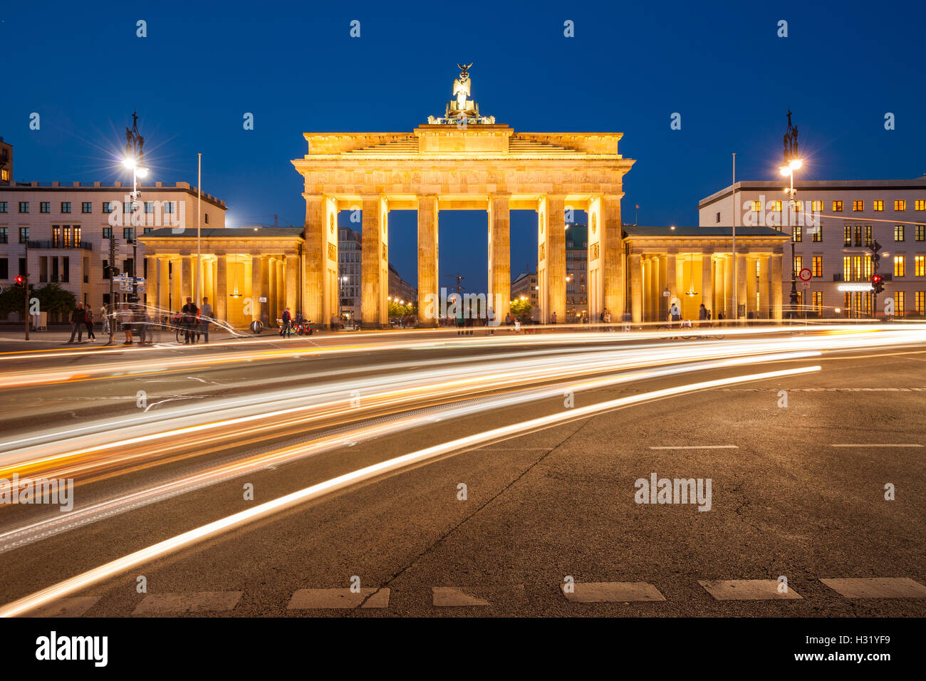 Berlin's Brandenburg Gate at twilight with speeding traffic light trails - Stock Image