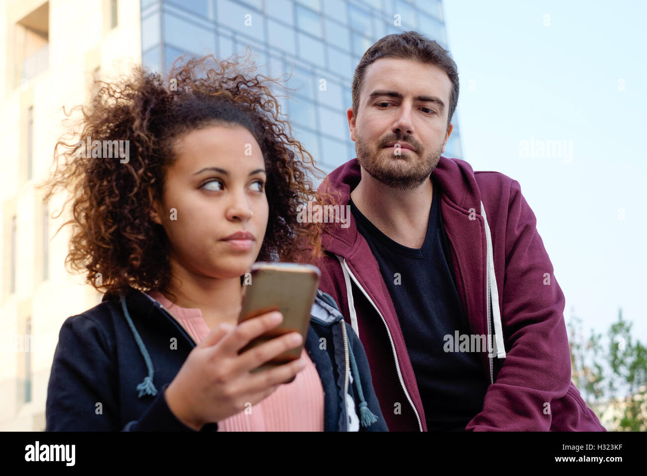 Boy spying his friend mobile phone - Stock Image