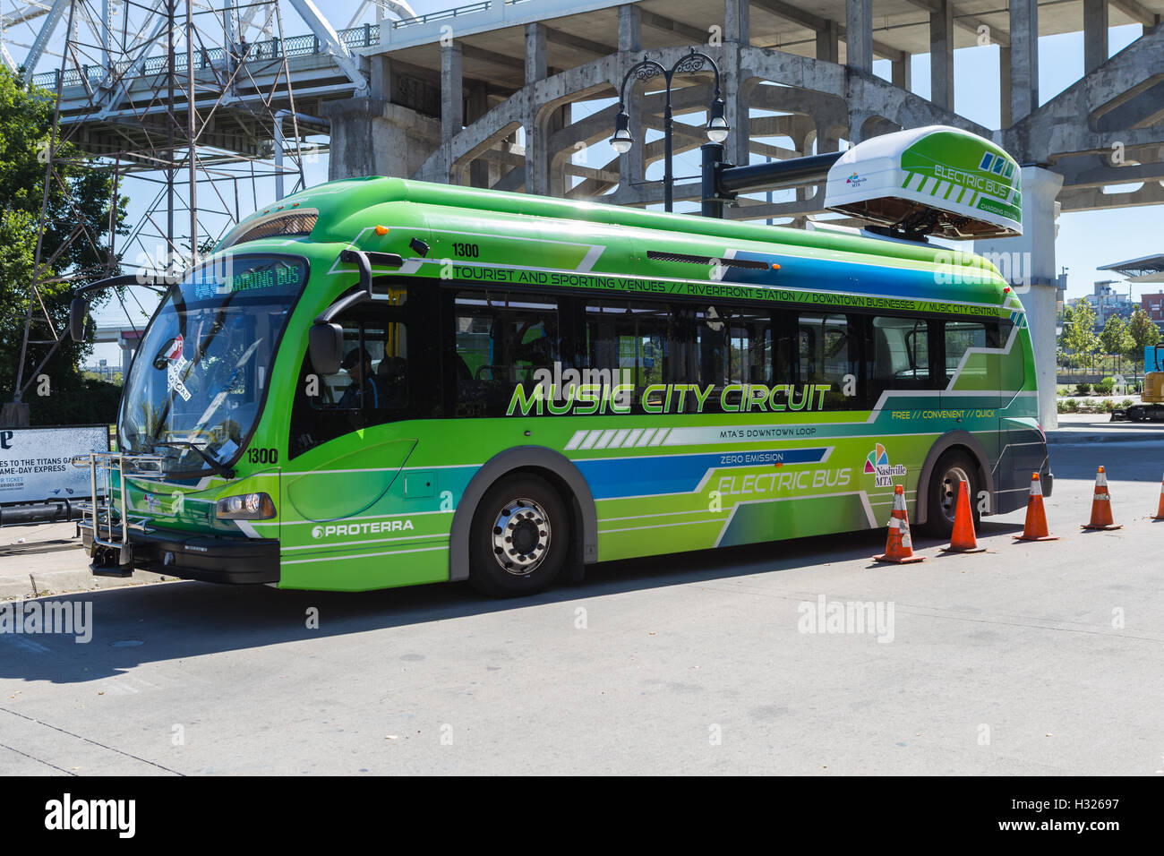 An electric Music City Circuit circulator bus charges at a bus charging station at Riverfront Station in Nashville, - Stock Image