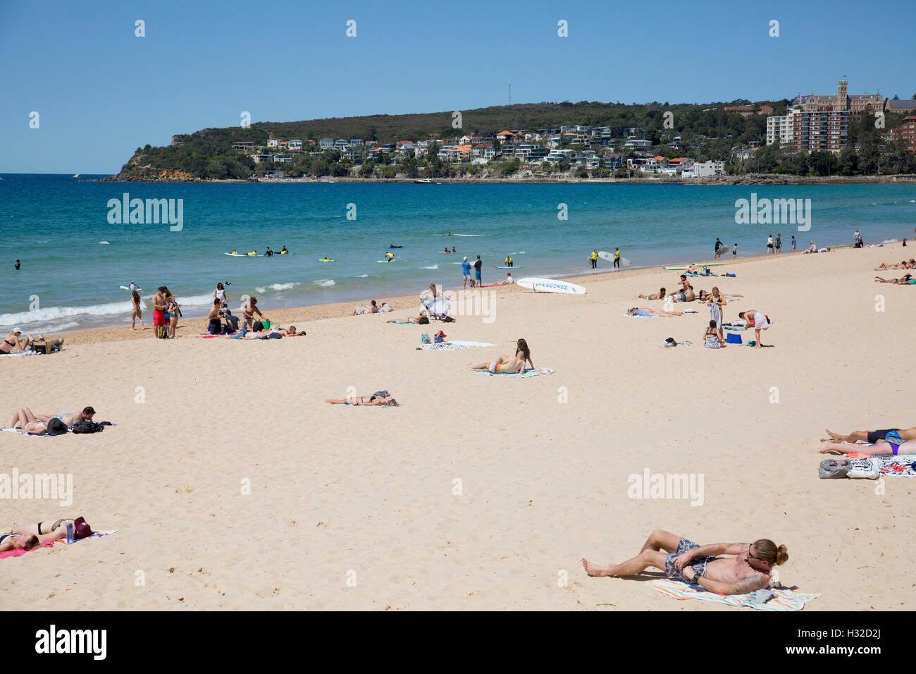 Australians sunbathing on Manly Beach, one of sydney's famous northern beaches,Australia - Stock Image