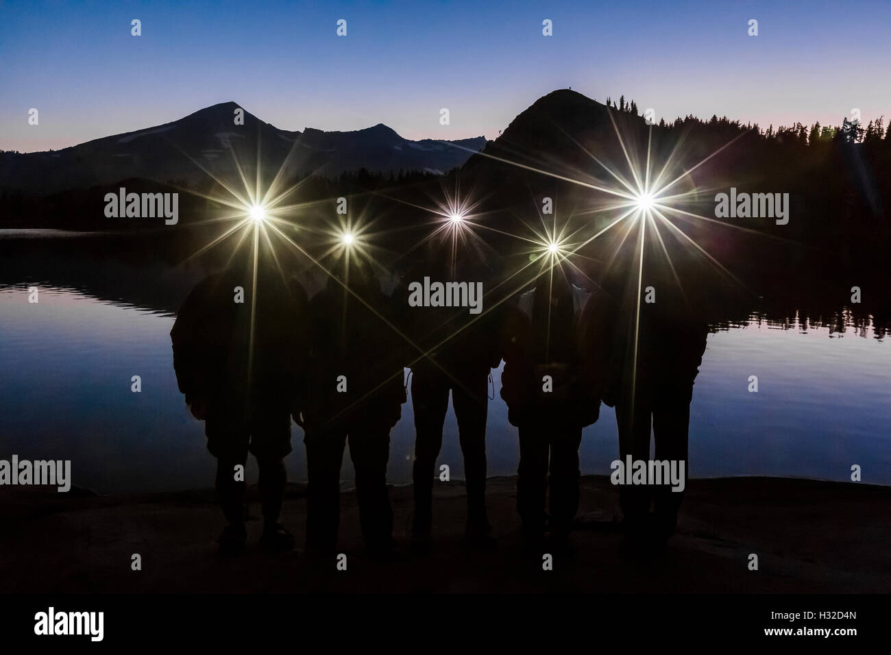 Group of five hikers with headlamps at deep twilight along Lake of the Woods, in the Desolation Wilderness, California, - Stock Image