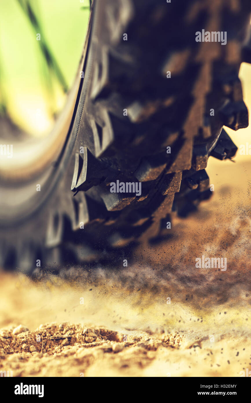 Mountain bike wheel close up with dirt dust particles, MTB bicycle ride through sandy ground - Stock Image