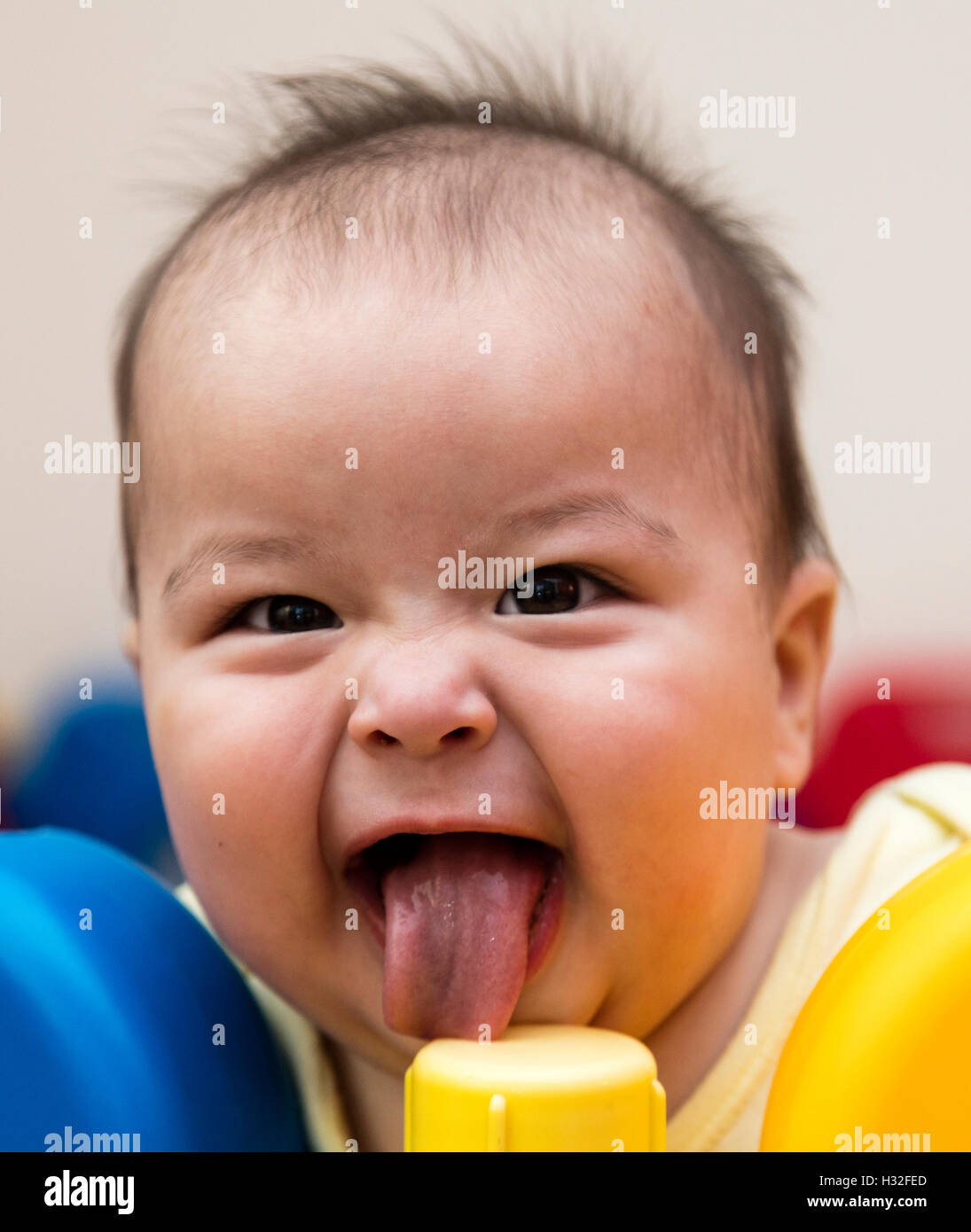 baby with funny grin licking plastic post in playpen - Stock Image
