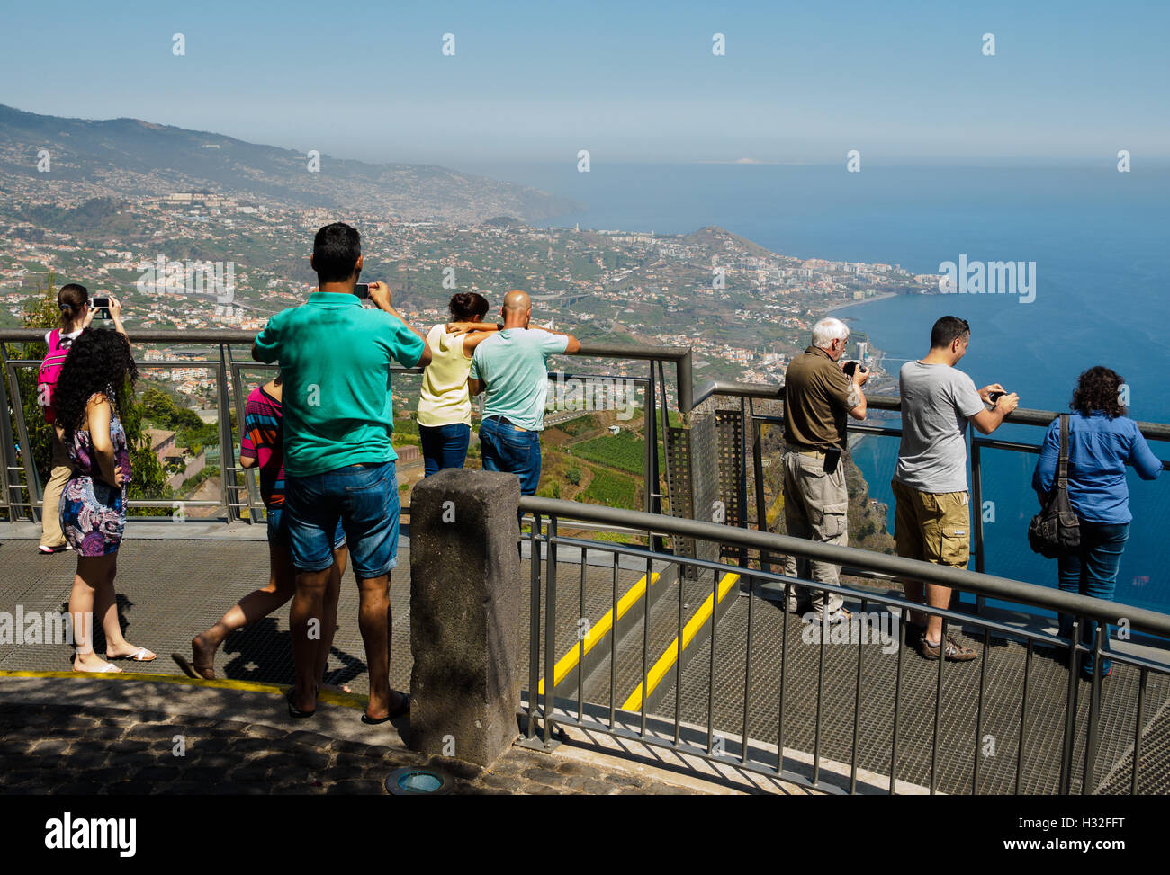 Tourists enjoy a view from the Miradouro do Cabo Girao, 580 meters above sea level, direction Camara de Lobos and - Stock Image