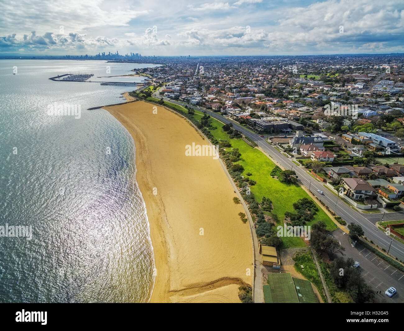 Aerial view of Brighton Beach coastline with Melbourne CBD skyscrapers in the distance - Stock Image