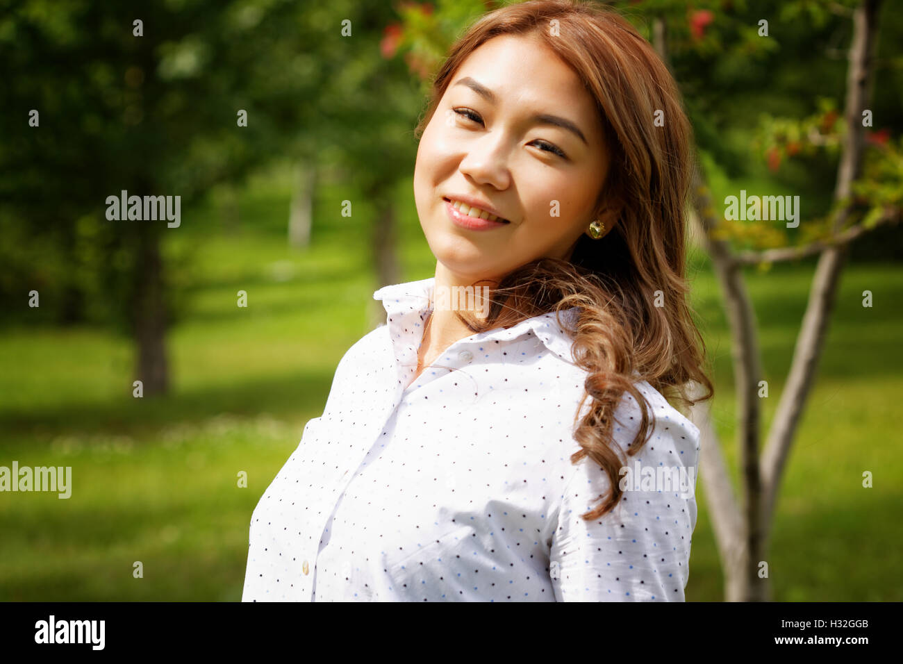 Beautiful kazakh woman walking in the summer park - Stock Image
