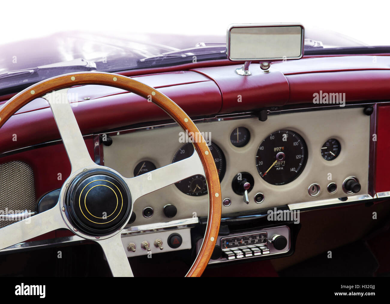Dashboard of an old classic car with round measuring instruments and wooden steering wheel - Stock Image