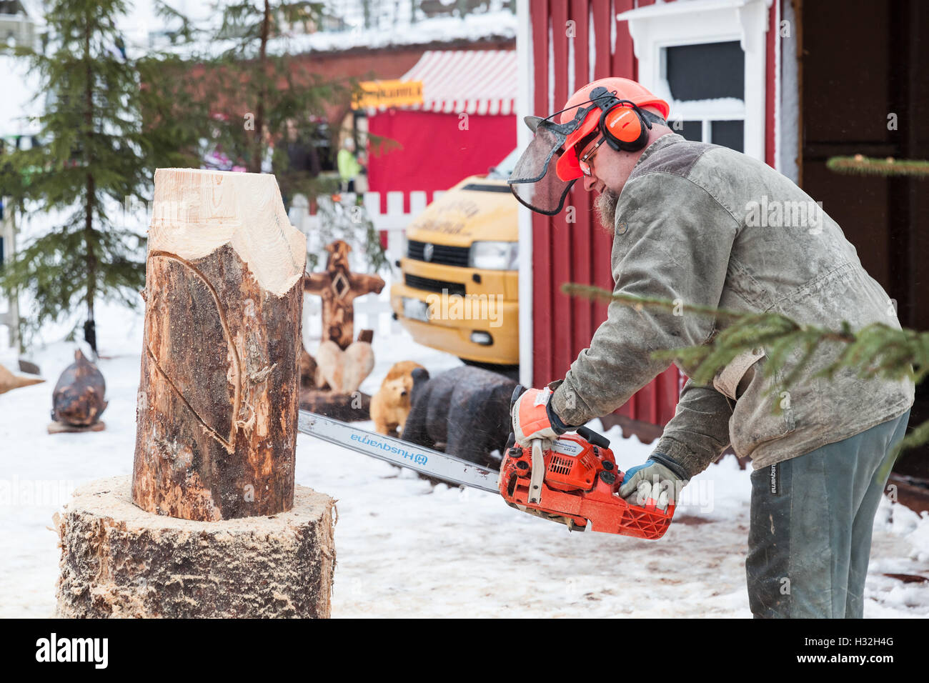 Hamina, Finland - December 13, 2014: Finnish master sculptor with a chainsaw produces rough wooden sculpture - Stock Image