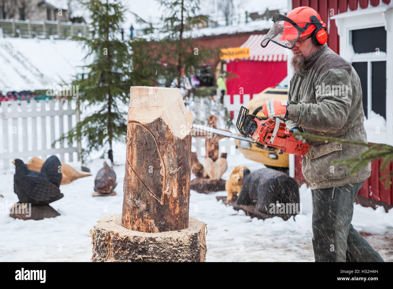 Hamina, Finland - December 13, 2014: Professional Finnish sculptor with a chainsaw produces wooden bird sculpture - Stock Image