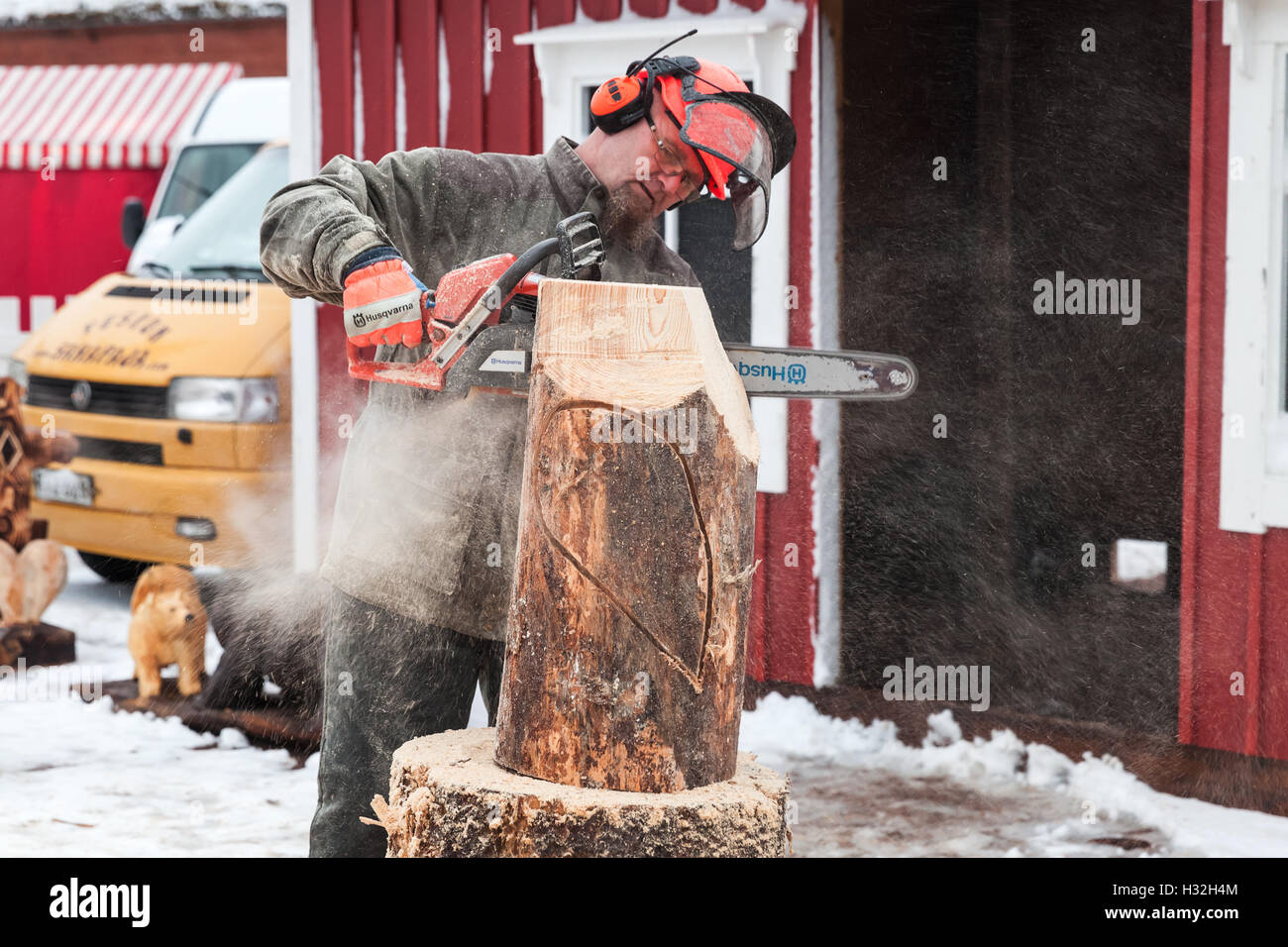Hamina, Finland - December 13, 2014: Master sculptor with a chainsaw produces wooden bird sculpture Stock Photo