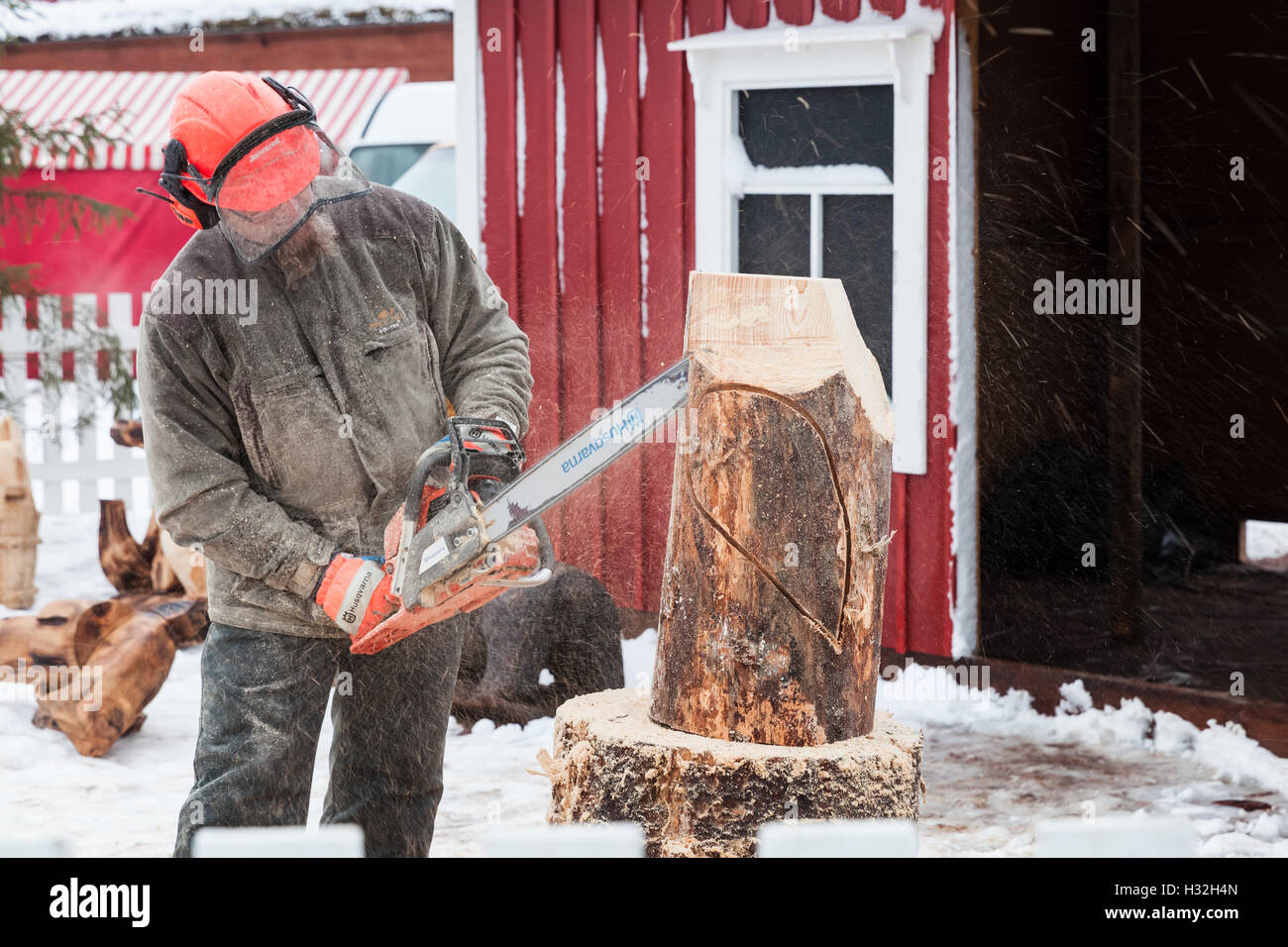 Hamina, Finland - December 13, 2014: Finnish sculptor with a chainsaw produces wooden sculpture - Stock Image