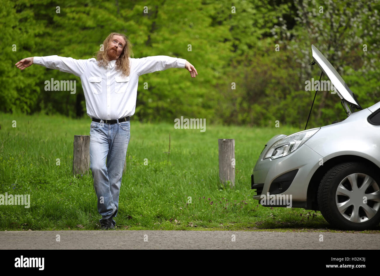 Funny driver praying a broken car by the road - Stock Image