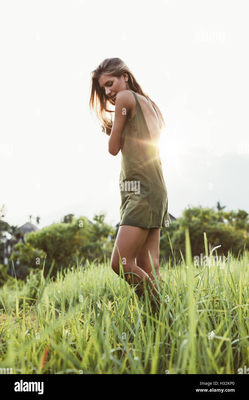 Full length shot of attractive young woman in field with sun shining in background. Female fashion model outdoors - Stock Image