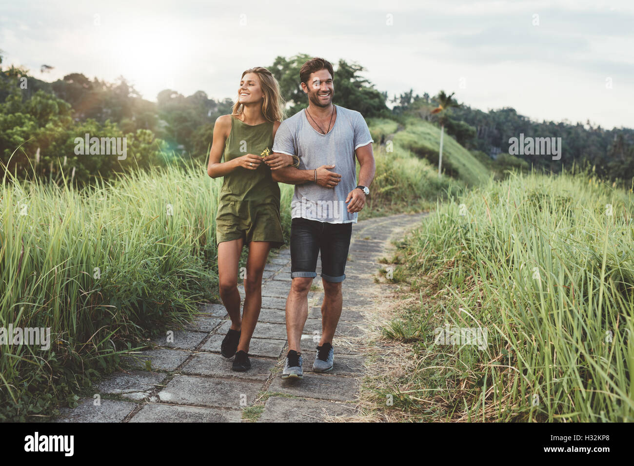 Outdoor shot of young couple in love walking on pathway through grass field. Man and woman walking along tall grass - Stock Image