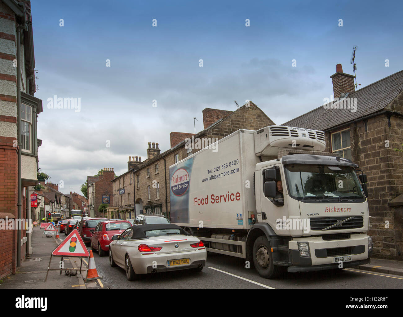 Roadworks in narrow street in English village of Belper with traffic lights, signs, and traffic congestion with - Stock Image