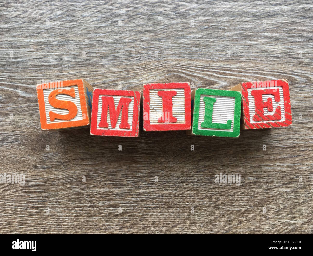 Alphabet wood block letters forming the word SMILE , it is a