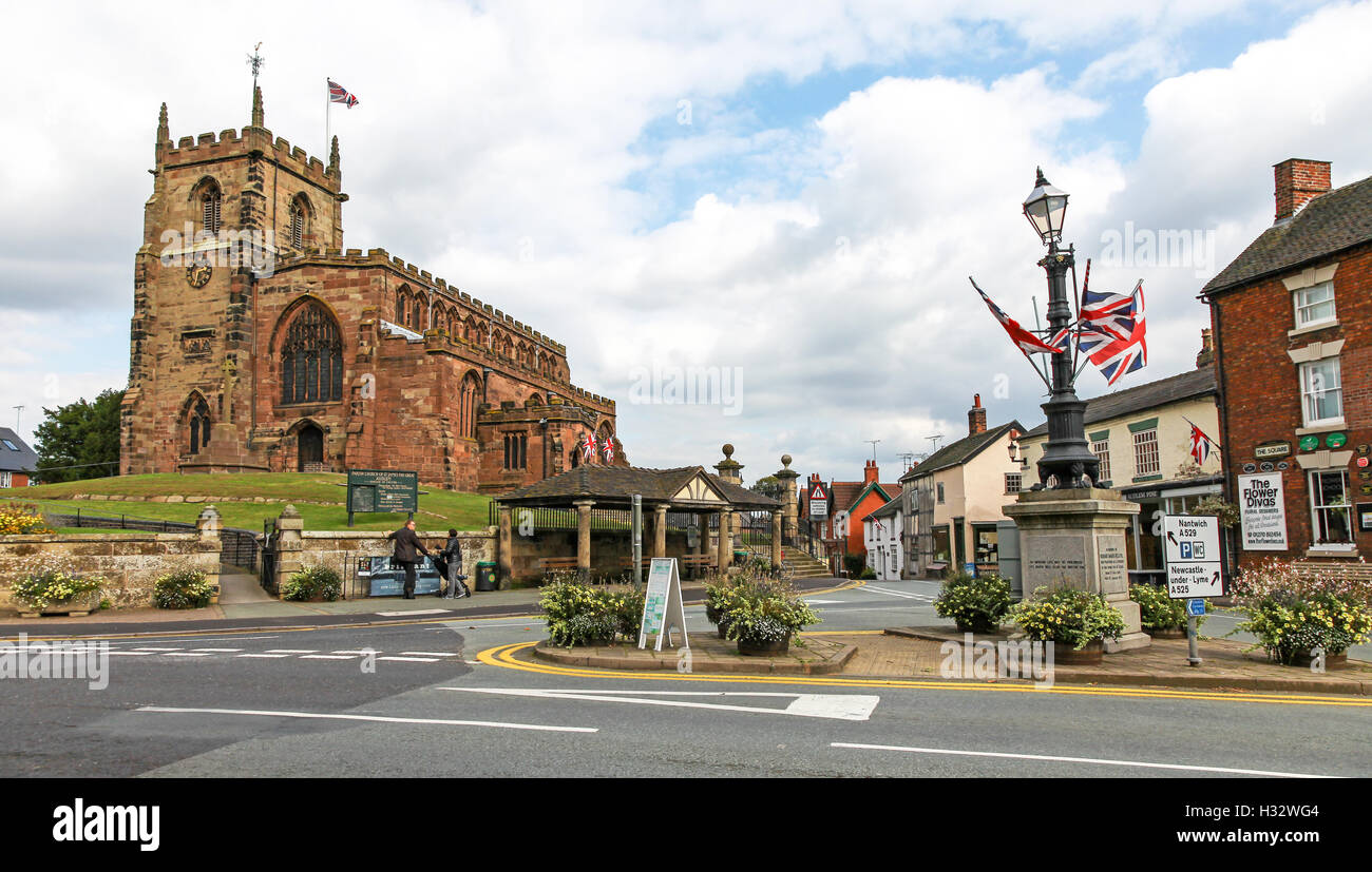 Parish Church of Saint James the Great and the war memorial in the centre of the village of Audlem Cheshire England - Stock Image