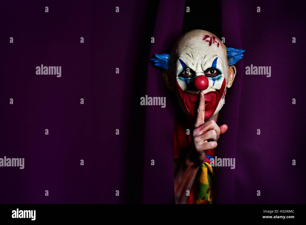 a scary evil clown peering out from a purple stage curtain, with his forefinger in front of his lips, asking for - Stock Image