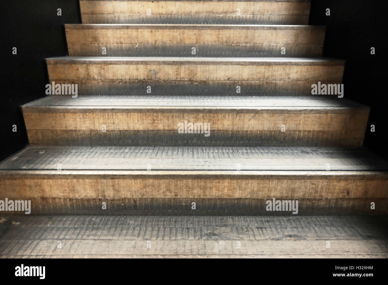 Set of light brown / beige concrete steps in a staircase leading upwards. - Stock Image