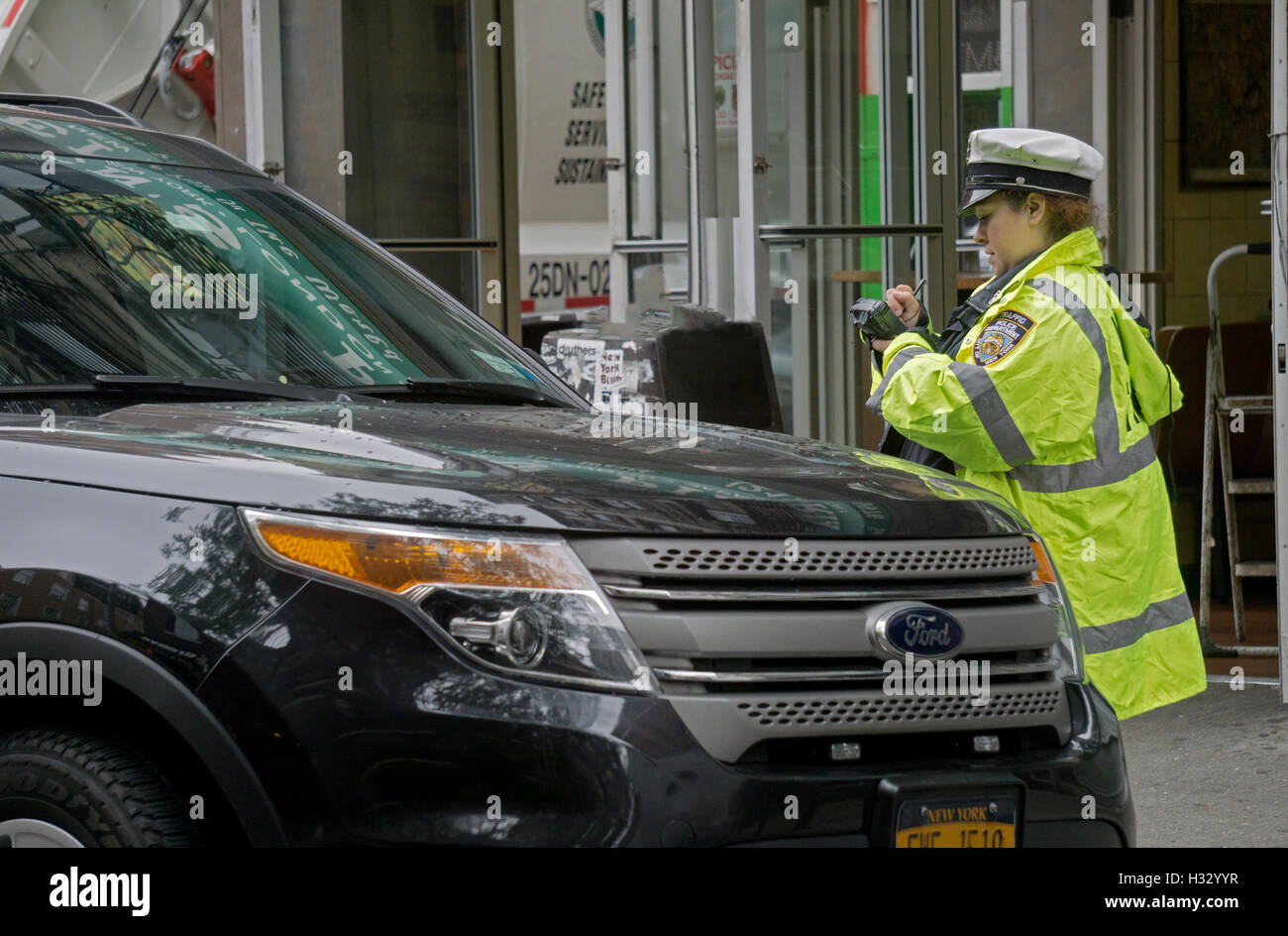 A New York City Police department traffic agent using a portable electronic ticket issuing machine on Bleeker St. - Stock Image