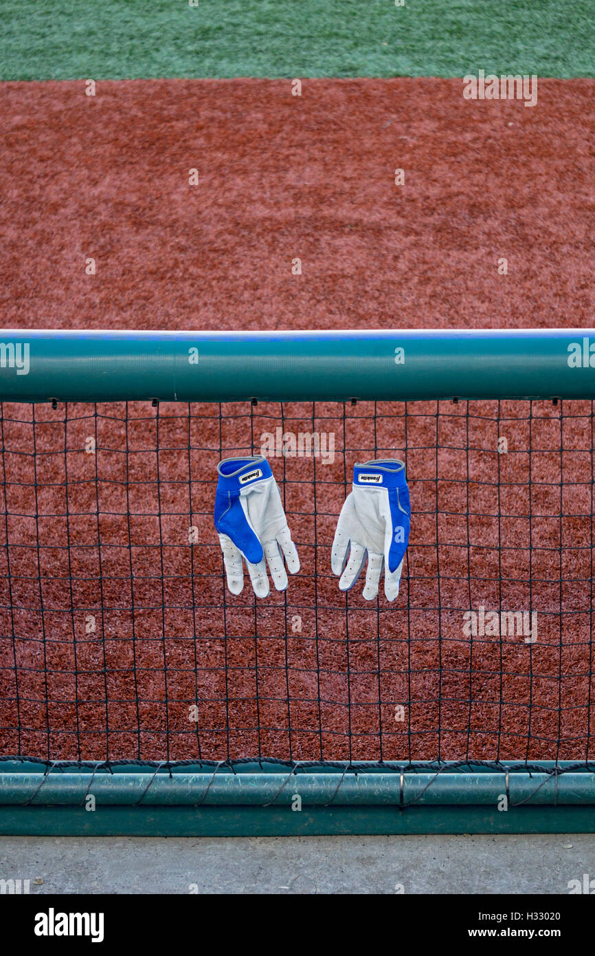 Baseball hitting gloves hanging on a fence near a dugout at MCU Park in Coney Island Brooklyn, NY at the World Baseball - Stock Image