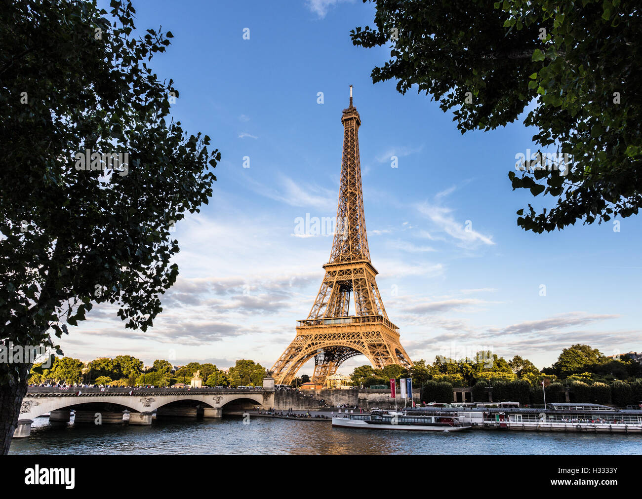 Sunset over the Eiffel Tower along the Seine river in Paris, France capital city. - Stock Image