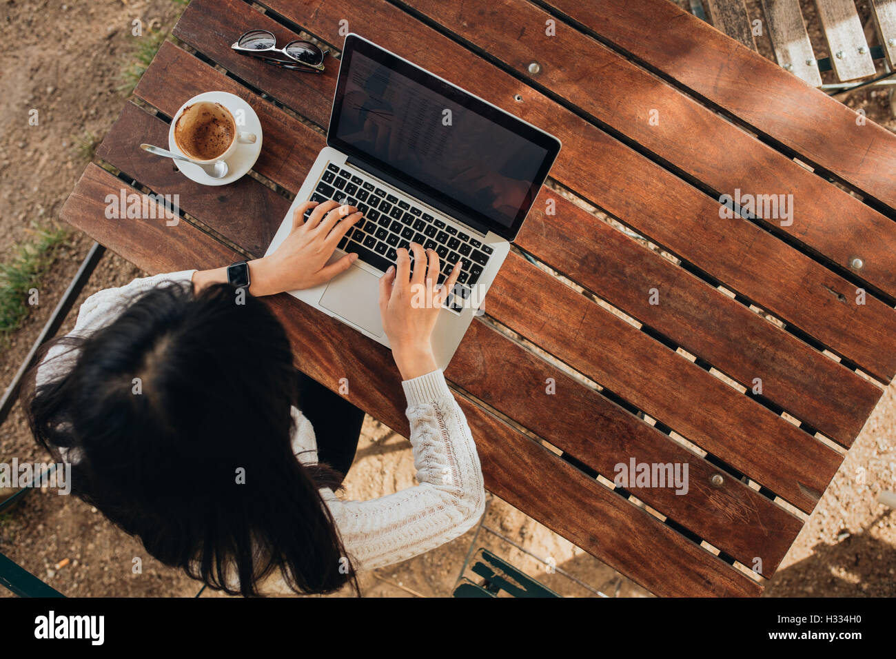 Overhead view of young female working on her laptop at a cafe. Top view shot of female sitting at a table with a - Stock Image