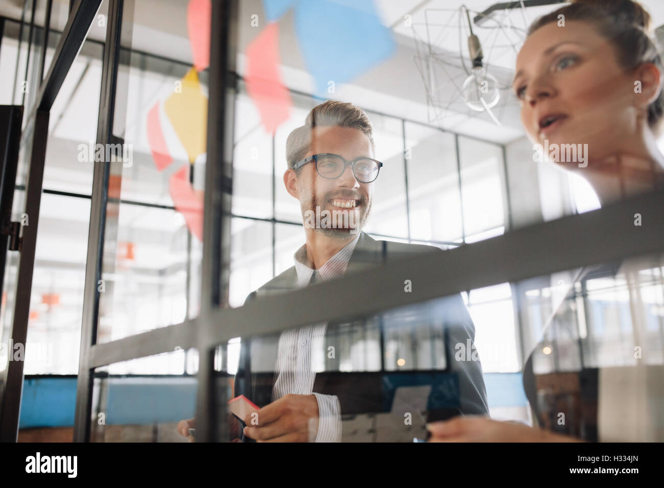 Two professional coworkers discussing new ideas on a glass wall. Creative professionals standing at the office behind Stock Photo