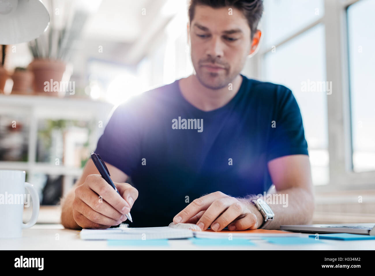Young male business executive writing down some important notes in diary at his desk. Young businessman updating - Stock Image