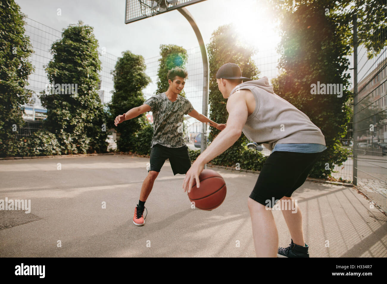 Young friends playing basketball together, boy in front of net blocking and other dribbling the ball on outdoor Stock Photo