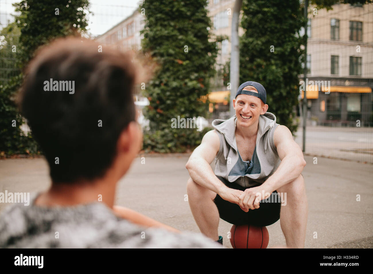 Smiling young guy sitting on basketball court and talking with friend. Two friends relaxing after playing basketball - Stock Image