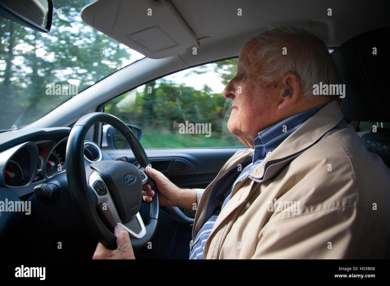 Close up of elderly man (aged 83) driving his automobile, United Kingdom - Stock Image