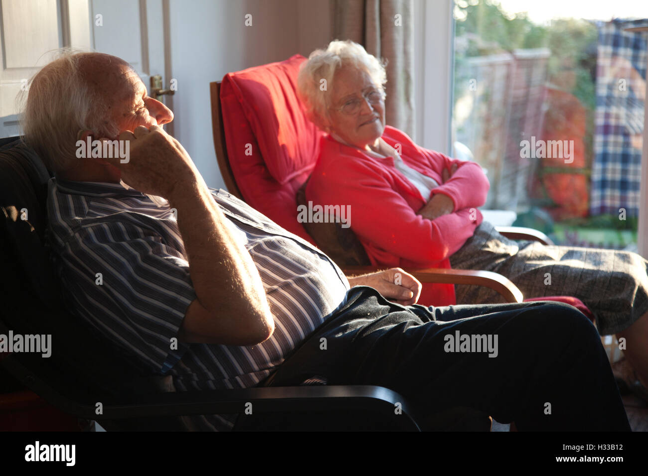 Elderly couple sat inside enjoying the afternoon sun which is shining through the windows of their home, Southwest - Stock Image
