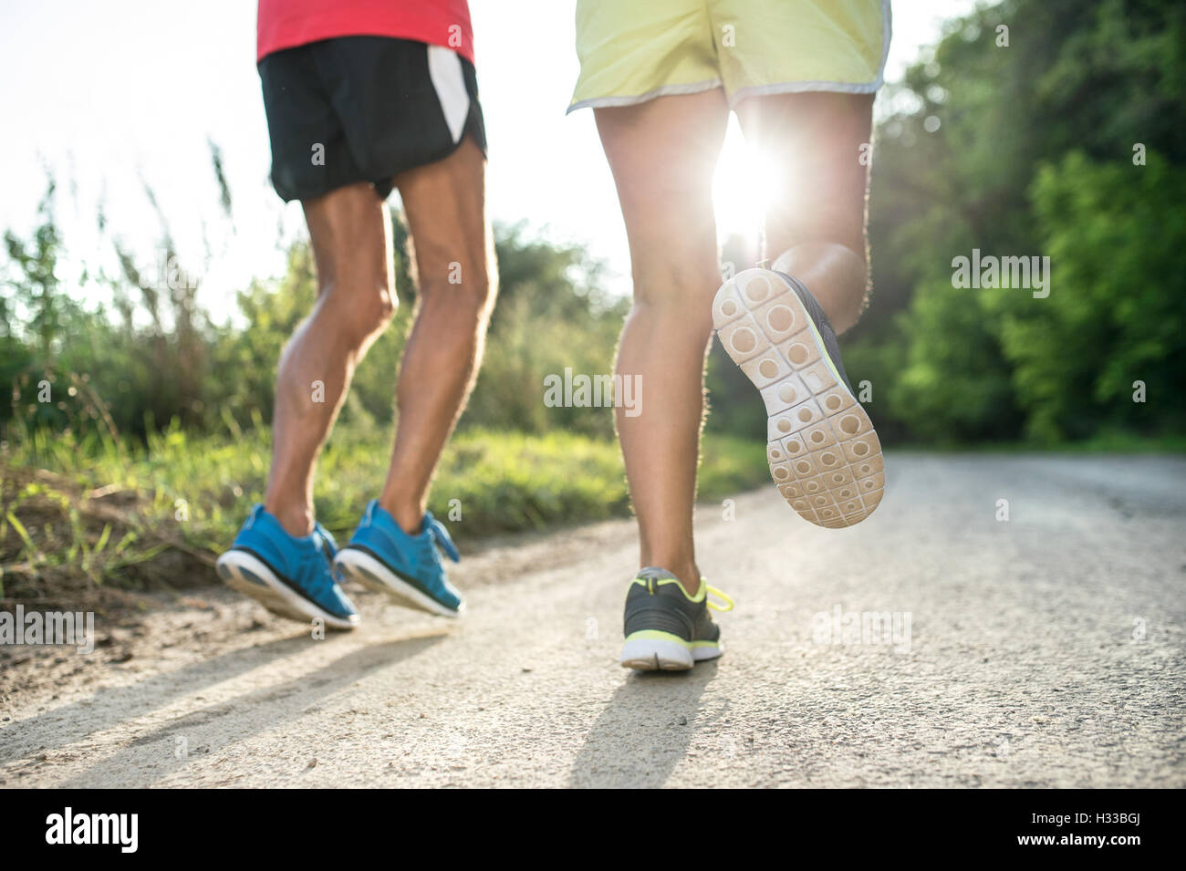 Unrecognizable senior couple running outside in sunny nature - Stock Image