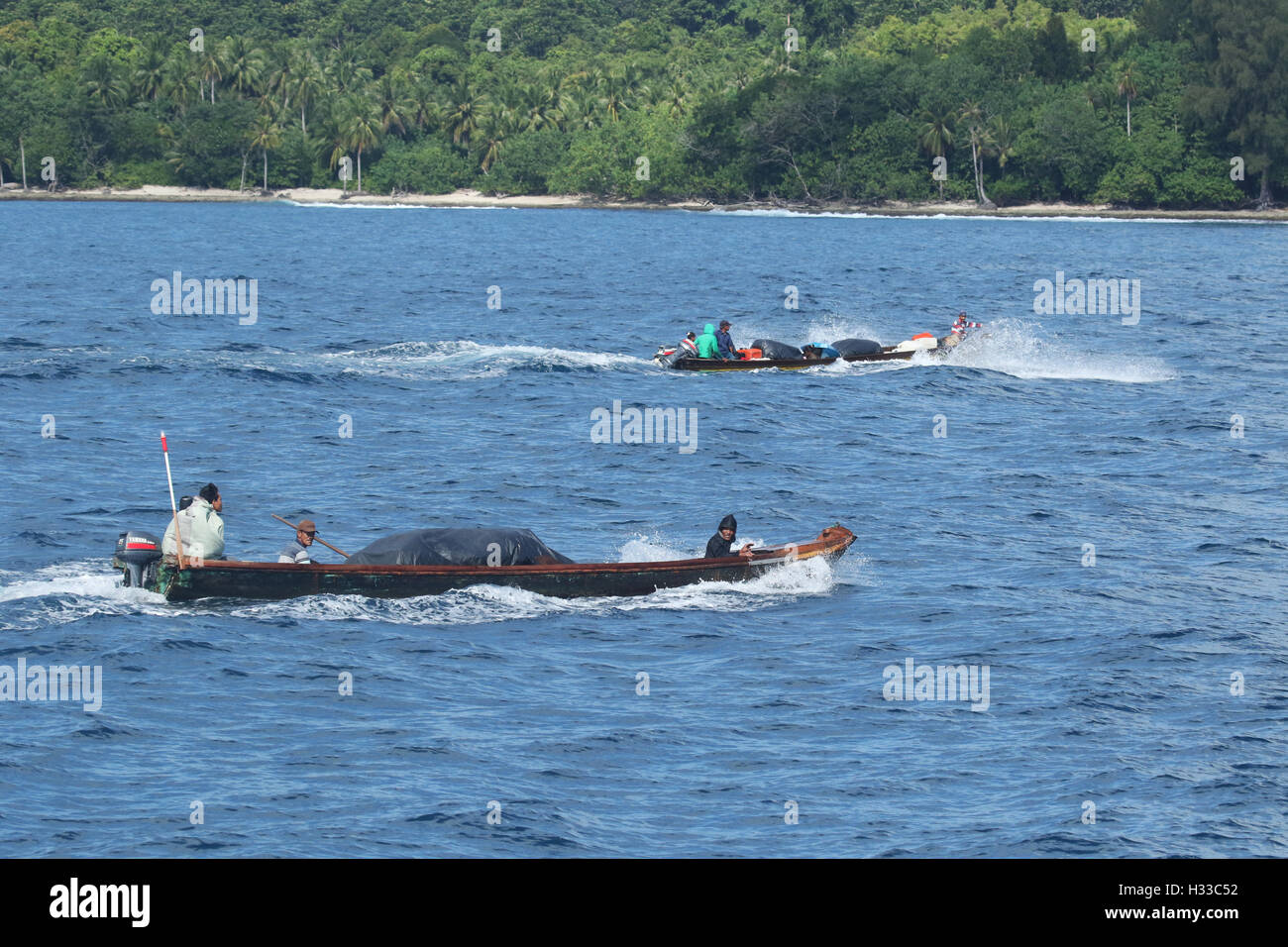 Mentawai Island Fishermen returning home with their families and fish - Stock Image