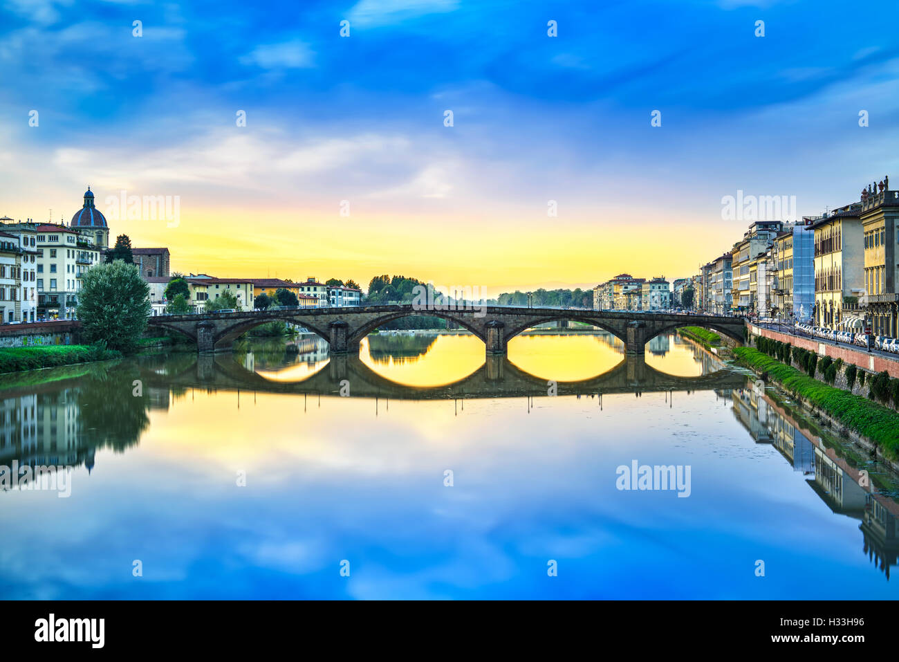Florence, Ponte alla Carraia medieval Bridge landmark on Arno river, sunset landscape with reflection. It is the - Stock Image