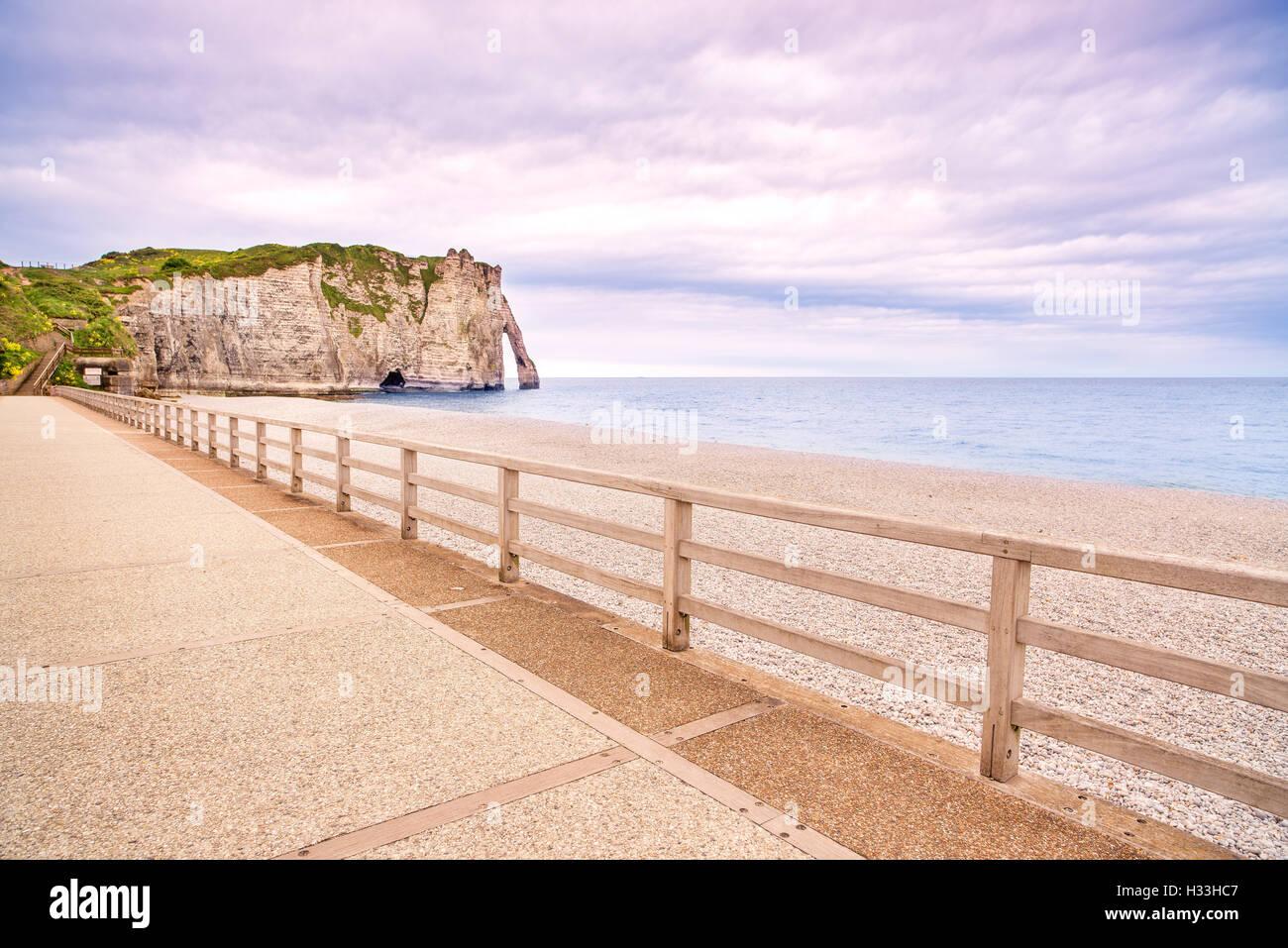 Etretat Aval cliff landmark, balcony and beach under a cloudy sky. Normandy, France, Europe. - Stock Image