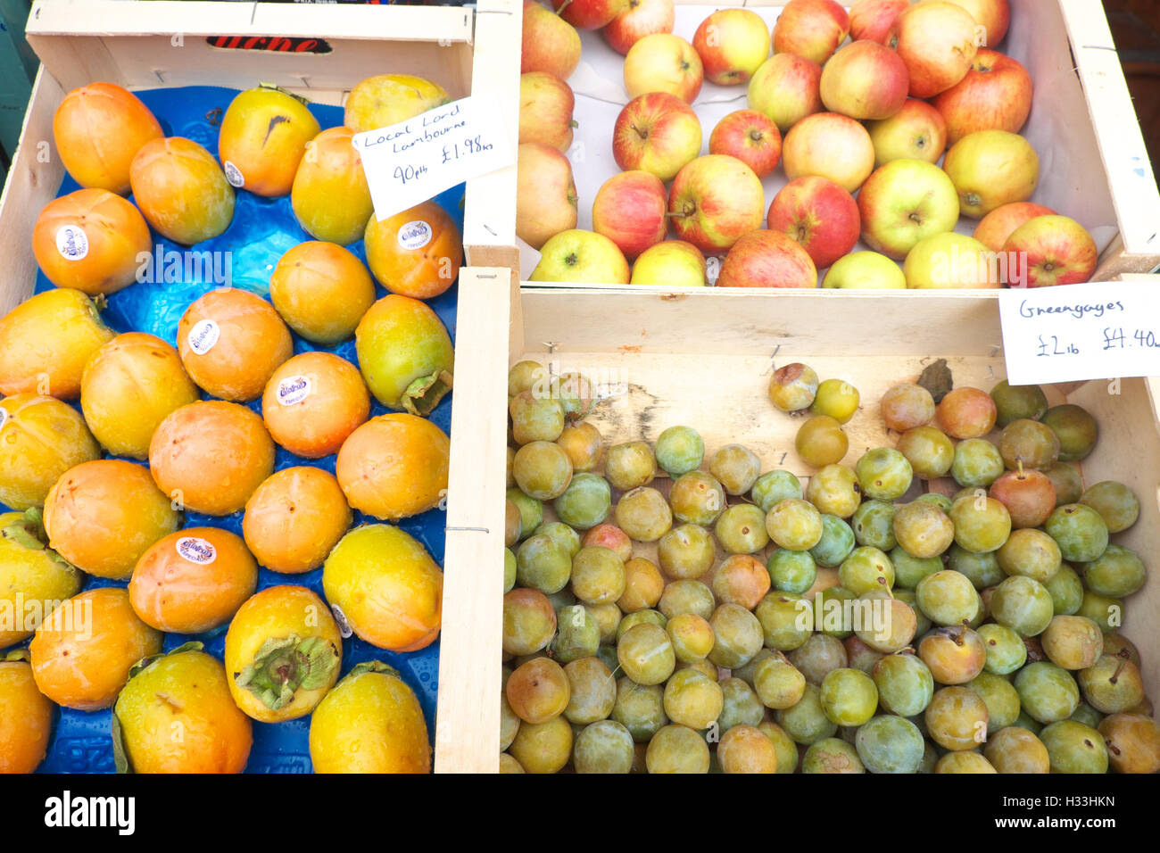Greengrocers display showing persimmon fruit on left, greengages lower right and apples top right - UK - Stock Image