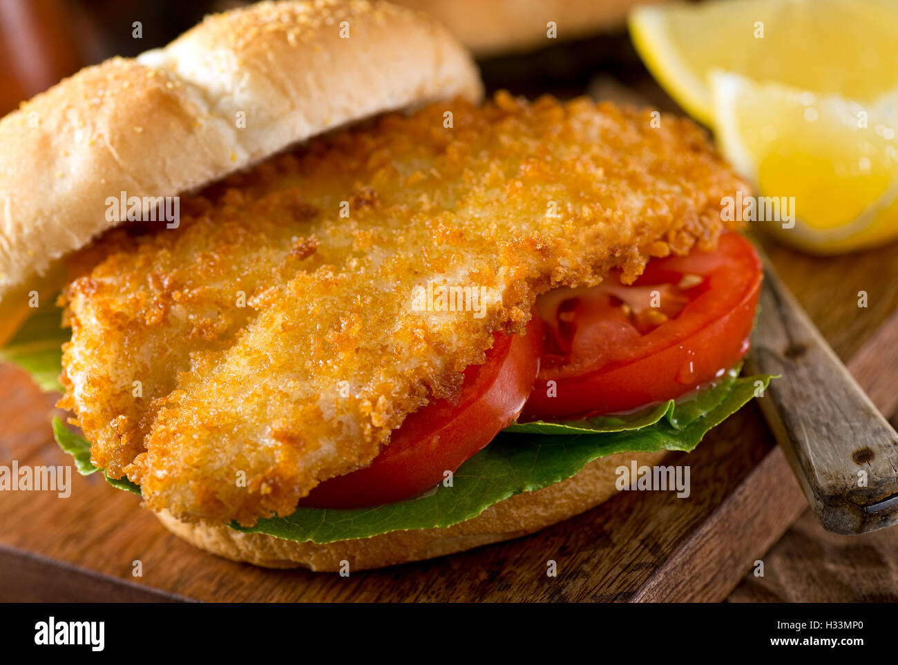 A delicious homemade fish burger with lettuce and tomato on a bun. - Stock Image