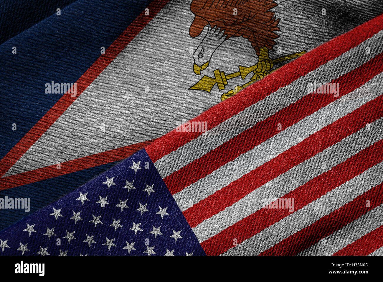 3D rendering of the flags of USA and American Samoa on woven fabric texture. American Samoa is a U.S. territory. Stock Photo
