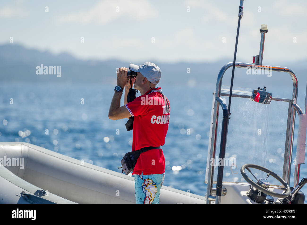 Sailing race referee on the RIB is watching at his binocular - Stock Image