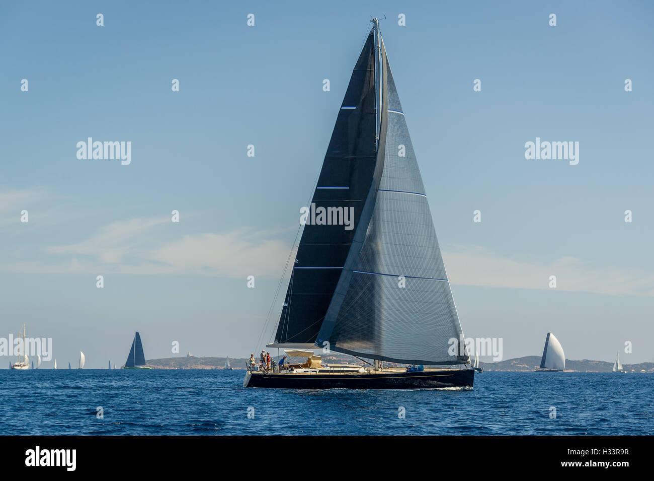 Luxury big sailing yacht with black sails. - Stock Image
